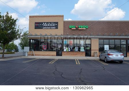 SHOREWOOD, ILLINOIS / UNITED STATES - AUGUST 16, 2015: One may sign up for T-Mobile cell phone service, and purchase custom t-shirts at Big Frog, in a strip mall in Shorewood.