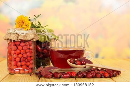 In glass jars of rowan berries, wild rose and cup of tea on a background of autumn leaves.