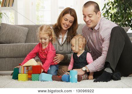 幸せな家族の 4 階にリビング ルームのソファの前の床の上に座って。