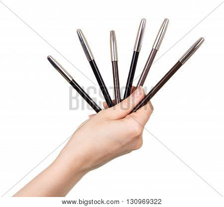 Eyebrow pencils in a female hand isolated on white background.