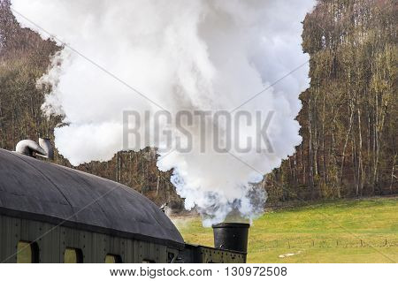 Steam engine locomotive pulls a railroad train.