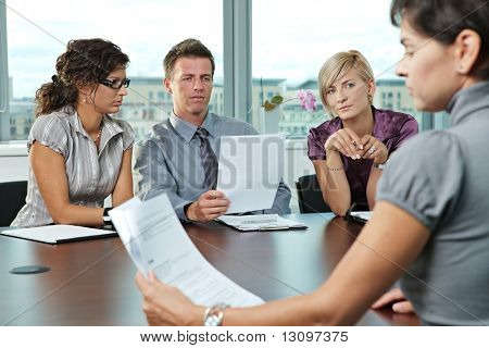 Panel of business people sitting at table in meeting room conducting job interview looking at documents.