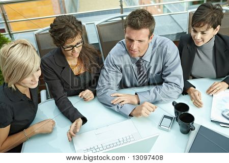 poster of Group of young business people sitting around table on office terrace outdoor, talking and working together. Overhead view.