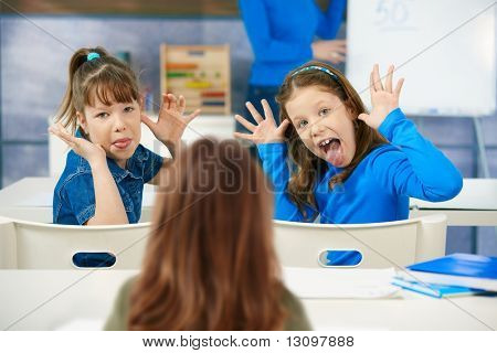 Elementary age schoolgirls pulling faces to girl sitting behind, teacher at blackboard in background.
