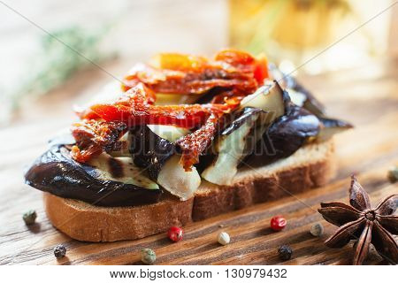 Vegetarian sandwich with sun-dried tomatoes and eggplant on wooden table. Front view. Closeup of bruschetta with grilled eggplant and sun-dried tomatoes on wooden background witn spices