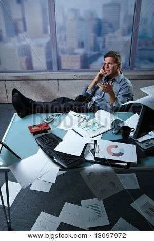 Tired businessman calling from office with shoes off fees up on table papers lying all around, picture taken from high angle.