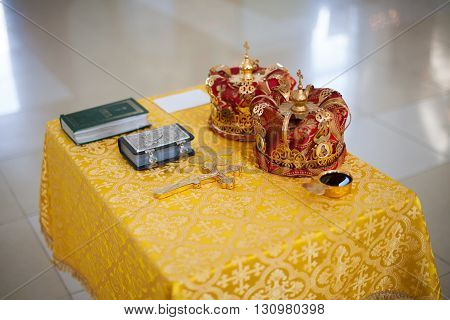 Orthodox Church wedding paraphernalia on table - cross, bible and crowns