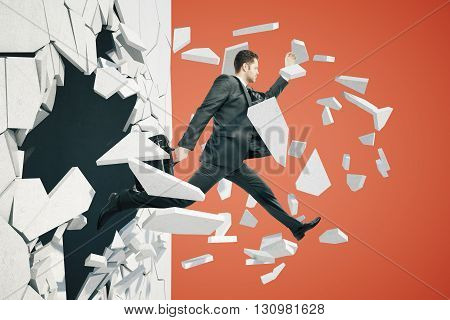 Business breakthrough success concept with businessman jumping through wall on red background