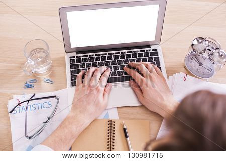 Male using blank white laptop placed on wooden desk with alarm clock water glass business report and other items. Mock up