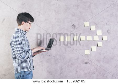 Side view of concentrated caucasian man using laptop next to sticker arrow glued onto concrete wall