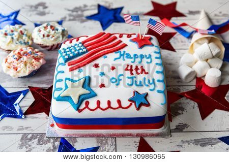 4th of July celebration cake with cupcakes and marshmallows on white, wooden surface