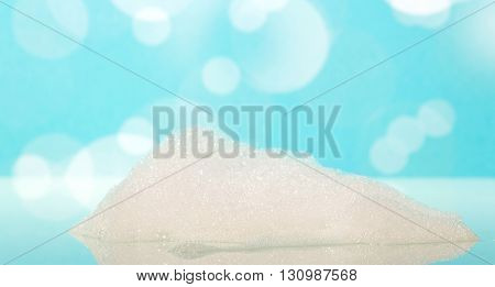The soap foam in a bathtub on the abstract blue background.