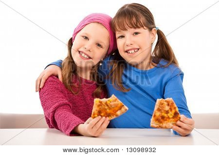 Girls smiling at table eating pizza slices.
