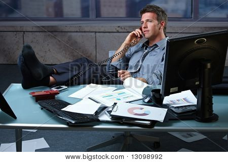 Tired businessman taking break speaking on landline phone with shoes off feet up on office desk holding glasses.