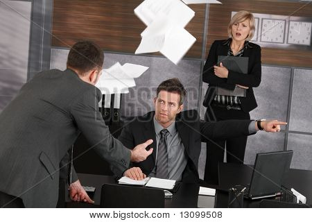 Angry boss firing employee, showing door. Papers flying in air, scared secretary standing in background.