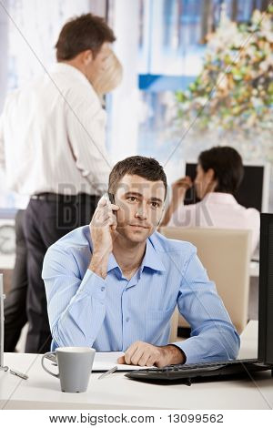 Businessman sitting at desk in office, talking on mobile phone.