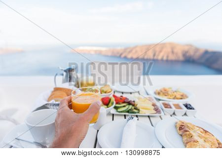 European vacation healthy breakfast food selfie. POV of man drinking morning orange juice at resort restaurant. Table for two on outdoor hotel balcony caldera view on Oia Santorini, Greece, Europe.