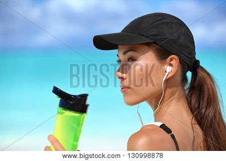 Healthy sporty Asian runner woman running on beach drinking water bottle listening to music with earbuds and smartphone wearing sun cap for solar protection during summer. Active living.