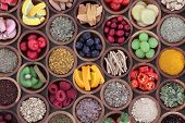 Health and super food  to boost immune system in wooden bowls, high in antioxidants, anthocyanins, minerals and vitamins. Also good for cold and flu remedy. poster