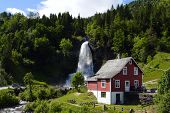 traditional norwegian wooden house with waterfall in the distance poster