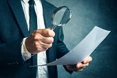 Tax inspector investigating financial documents through magnifying glass forensic accounting or financial forensics inspecting offshore company financial papers documents and reports. poster