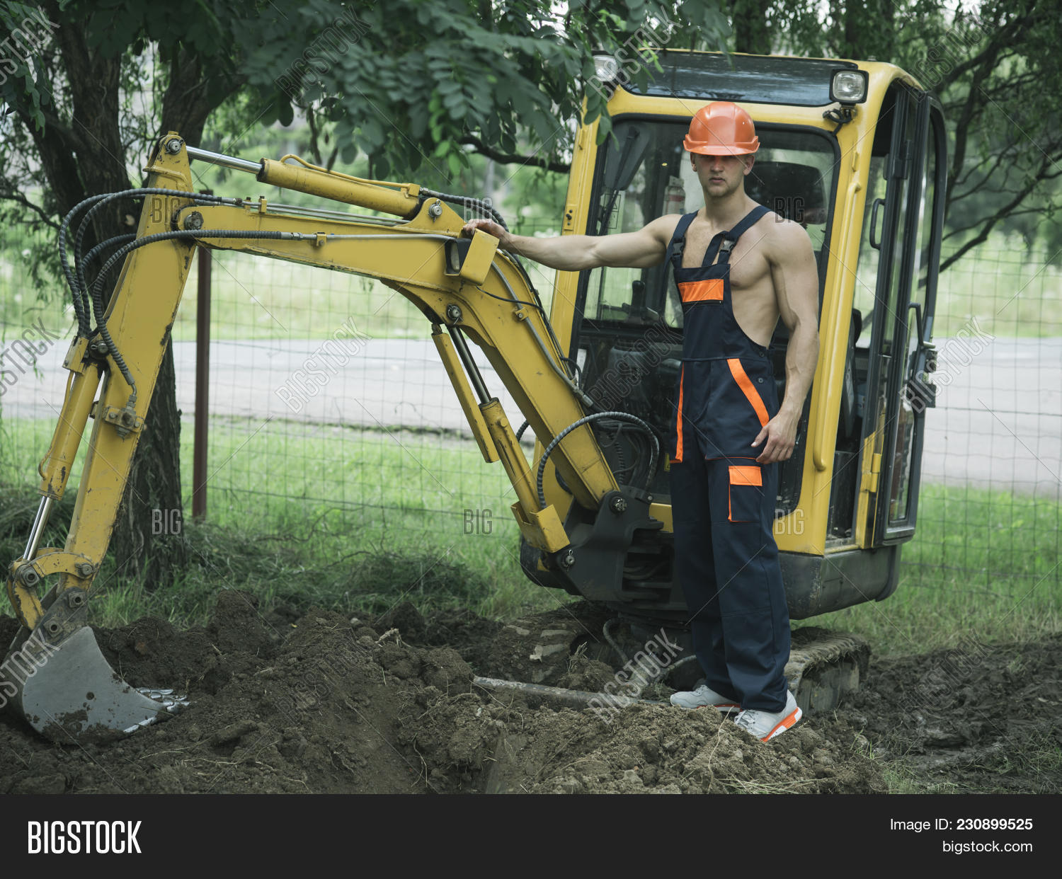 Sexy Man With Nude Torso Near Construction Equipment Or Excavator On Background Builder Concep