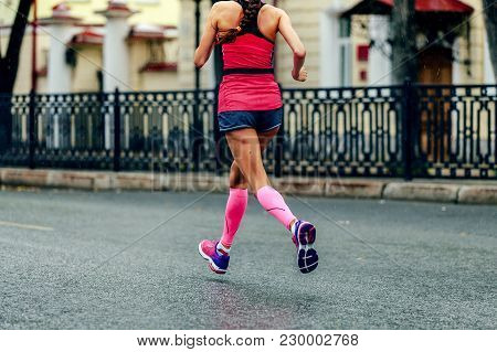 Female Runner In Pink Compression Calf Sleeves Running Marathon Under Rain Drops