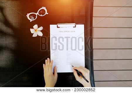 Sunny Flat Lay Of Woman Fill Visa Application For Travel, Sunlight Portrait With Sunglasses. And Flo