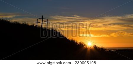 Three Cross On A Sand Hill As The Sunsets.