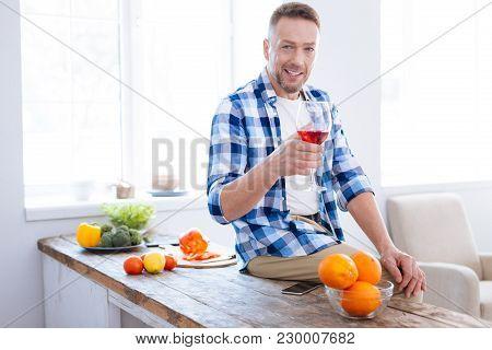 Enjoy Everyday. Charming Gay Vigorous Man Rising Glass Of Wine While Looking At Camera And Smiling