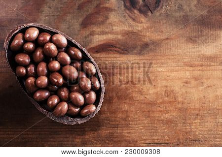 Chocolate Halved  Easter Eggs On Wooden Background With Chocolate Candies, Copy Space
