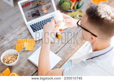Control Your Life. Top View Of Earnest Vigorous Handsome Man Rising And Studying Bottle With Drugs F
