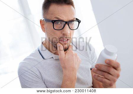 Biohacking Medication. Meditative Progressive Uncertain Man Posing On Light Background While Putting