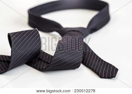 Black Tie Knotted In A Loop Shape On A White Background. The Concept Of Not Freedom