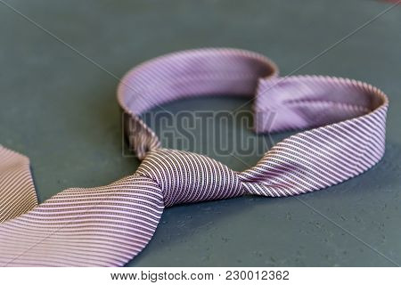 Pink Tie Is Tied In The Shape Of A Heart On A Gray Background. The Concept Of Love. Valentine's Day
