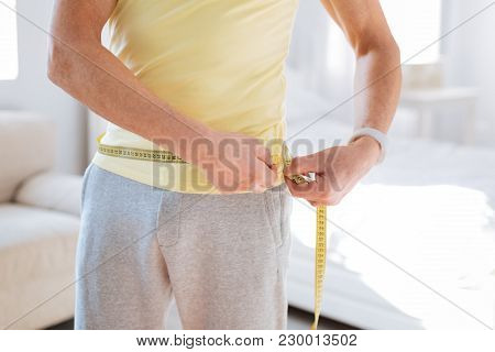 No Obesity Problem. Close Up Of Young Strong Male Hands Holding Metre Ruler While Fixing Progress Af