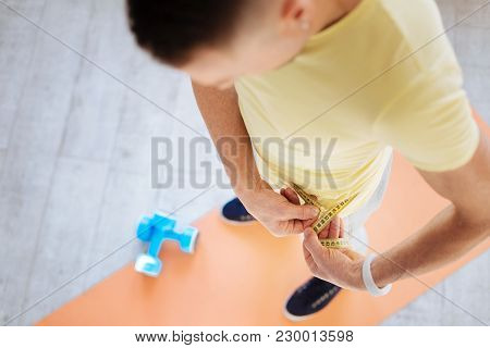 Resultative Biohacks. Top View Of Man Posing On Mat Board While Applying Metre Ruler And Looking Dow