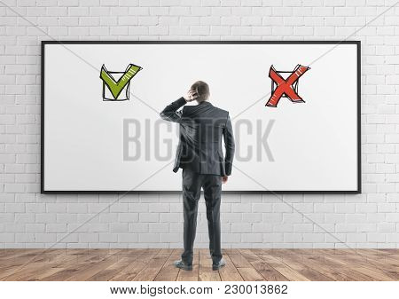 Rear View Of A Thoughtful Well Dressed Businessman Scratching His Head. Concept Of Confusion And A H