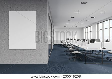 Computers On Office Cubicle Desks. Gray And Glass Walls With A Large Vertical Poster. A Dark Floor.