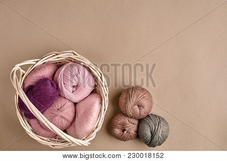 Balls Of Yarn And Knitting Needles. Colored Yarn For Knitting In A Wicker Bowl On A Beige Background