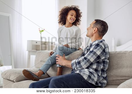 Happy Child. Nice Exuberant Curly-haired Girl Smiling And Sitting On The Couch And Talking With Her