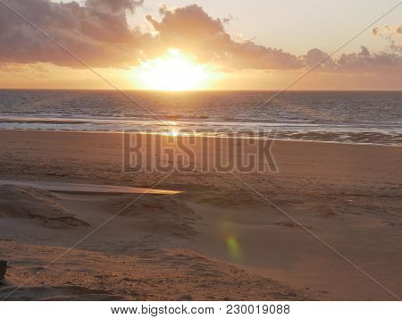 Sunset On The Beach With Cloudscape And Reflections On The Water