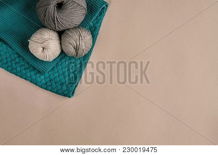 Grey And Turquoise Knitting Wool And Knitting Needles On Beige Background. Knitting As A Kind Of Nee