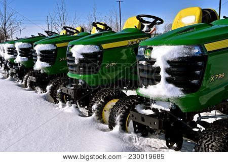 Moorhead, Minnesota, March 5, 2018: The John Deere  Lawn Tractors Covered With Snow Are Products Of