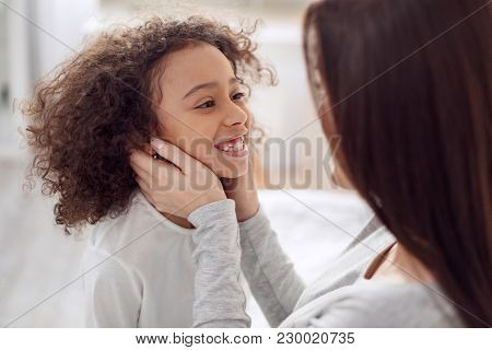 Being The Happiest. Attractive Exuberant Curly-haired Girl Smiling And Looking At Her Mother And Her
