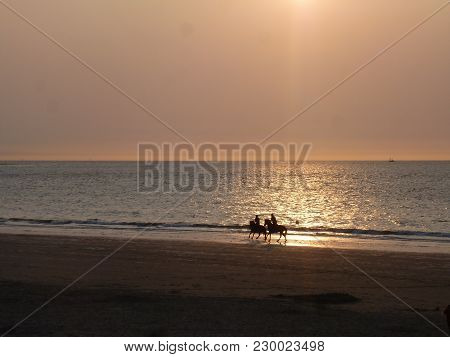 Sunset On The Beach With Two Riders And Reflections On The Water