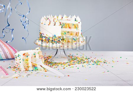 Confetti Birthday Cake With Colorful Sprinkles Over A Neutral Background.
