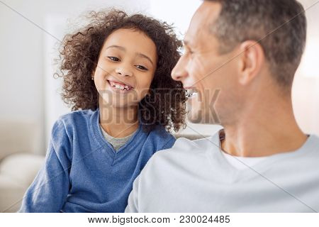 Pleasant Day. Beautiful Exuberant Curly-haired Girl Smiling And Talking With His Daddy While Sitting