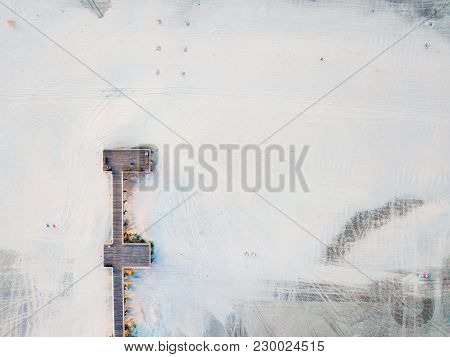 Wooden Dock On A Empty Beach Aerial View At Sunrise