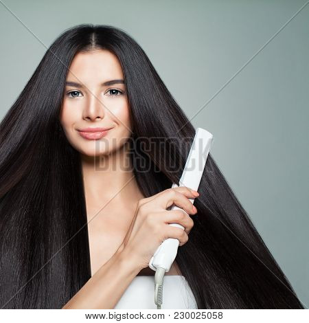 Hairdressing. Woman With Beautiful Long Straight Hair Using Hair Straightener. Cute Smiling Girl Str